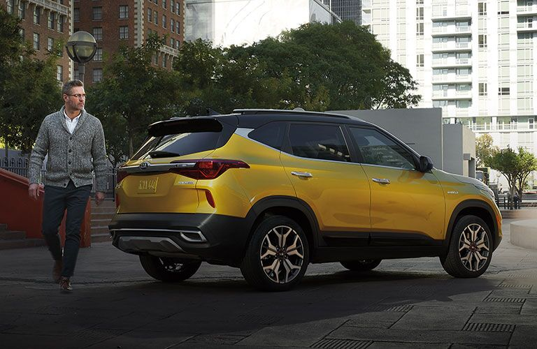 2021 Kia Seltos exterior mustard yellow parked in city with man in grey sweater walking away