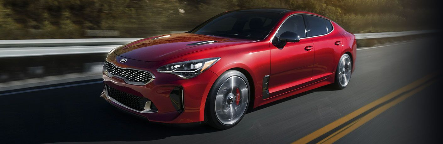 2020 Kia Stinger red driving down road with yellow lines_o