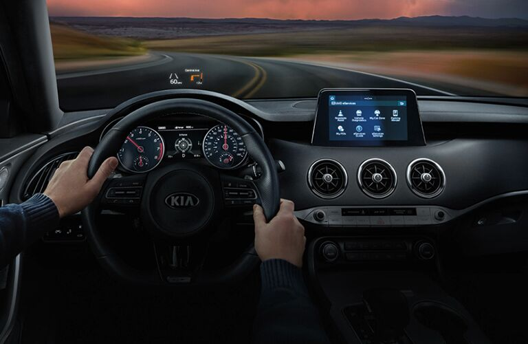 2020 Kia Stinger interior view of front cabin with hands on steering wheel