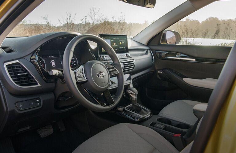 2021 Kia Seltos interior view through open driver side door showing dash board and center console