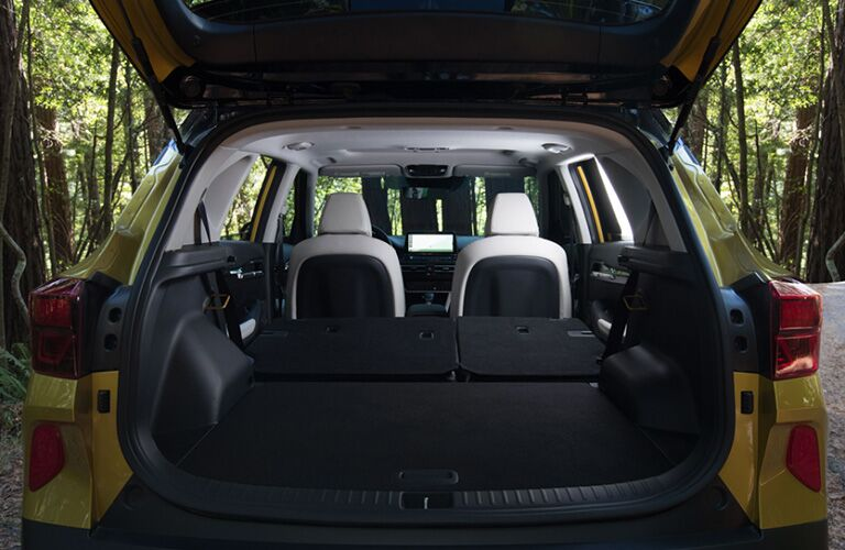 2021 Kia Seltos yellow trunk open view of back row of seats folded down in forest