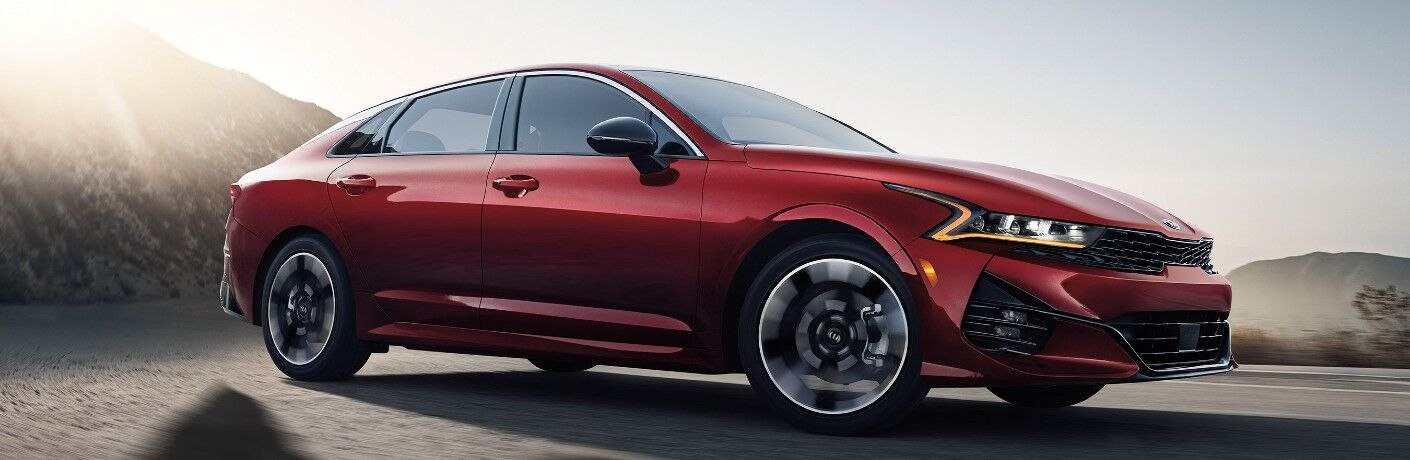 2021 Kia K5 exterior red driving on rocks with dust