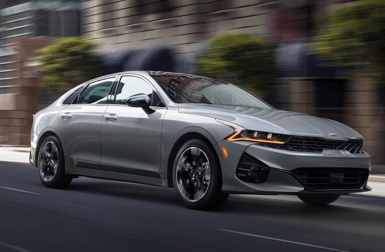 2021 Kia K5 gray driving down slanted road with motion blur