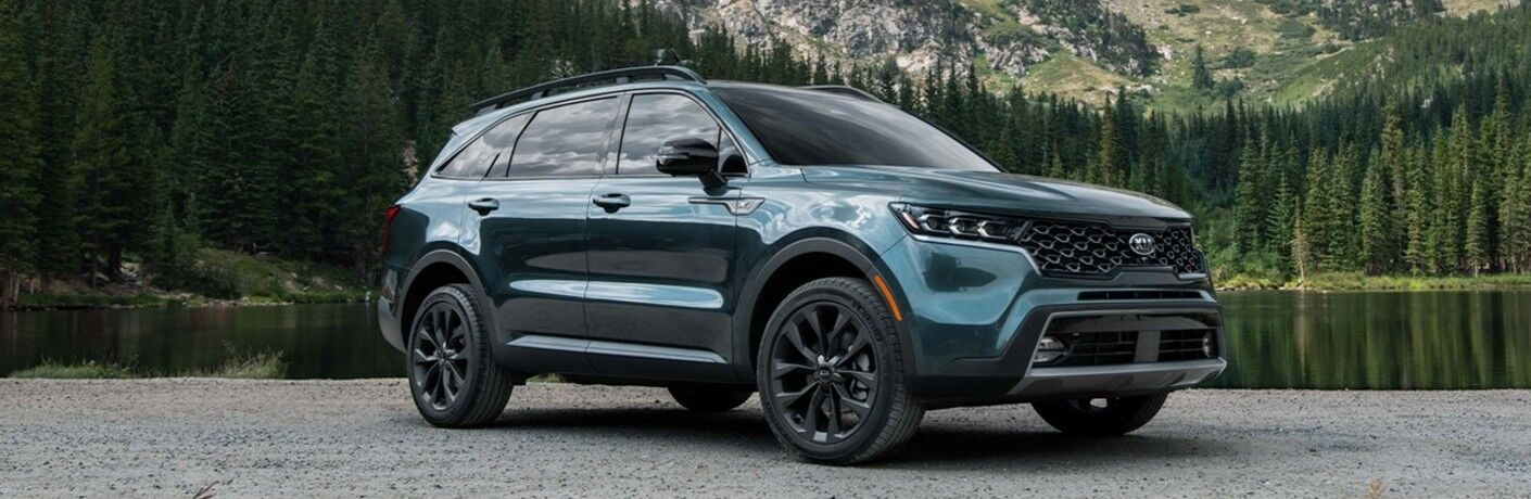 2021 Kia Sorento green parked in front of forest lake