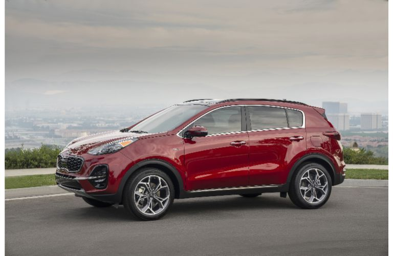 2021 Kia Sportage exterior side shot with dark red paint color parked on a hill with a fog city background