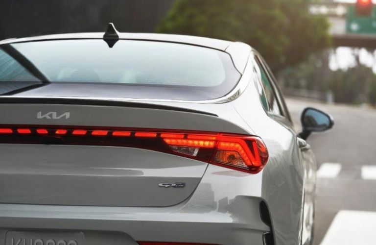 Back side view of the 2022 Kia K5 Gravity Gray moving on the road