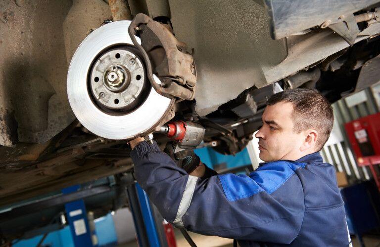 stock photo of man working on brake rotor in mechanic uniform