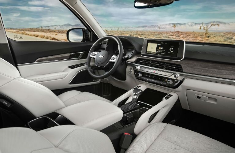 2020 Kia Telluride interior shot of front seating upholstery, steering wheel, and dashboard layout with infotainment screen