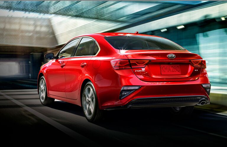 A red-colored 2021 Kia Forte driving on a road