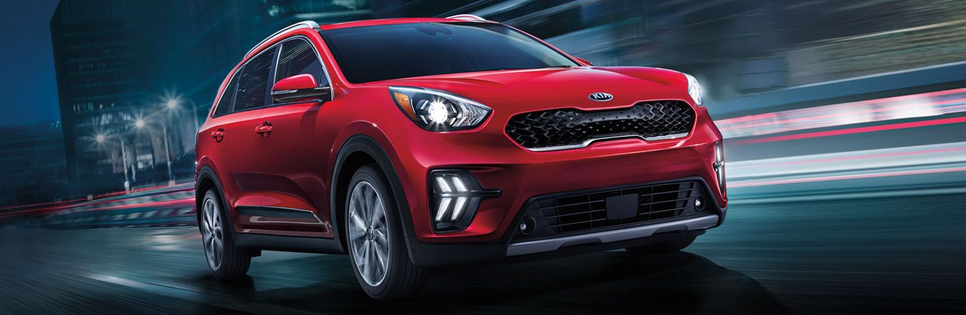 2020 Kia Niro red exterior front passenger side driving fast in city at night
