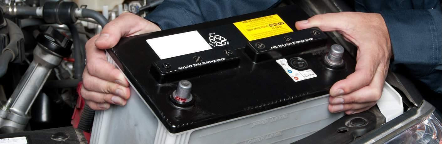 Service technician installing battery into a car