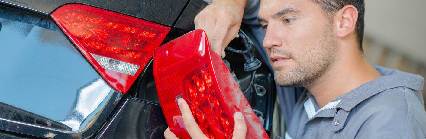Technician fixing a tail light