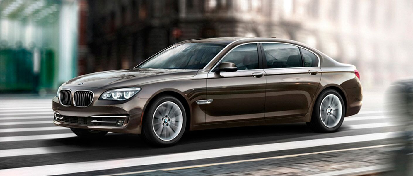 2014 BMW 7 Series exterior front fascia and drivers side on road with blurred building background