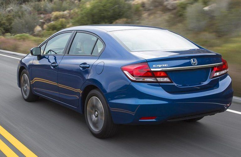 blue 2015 Honda Civic Sedan seen from the side and rear driving down the road