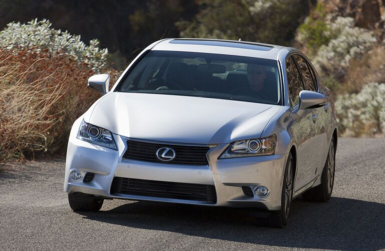 2015 Lexus GS 350 exterior front fascia and drivers side on road with flowering plants on roadside