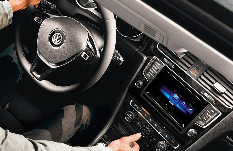 2015 VW Golf interior front cabin man with hand on steering wheel and shifter, close up of wheel and dashboard