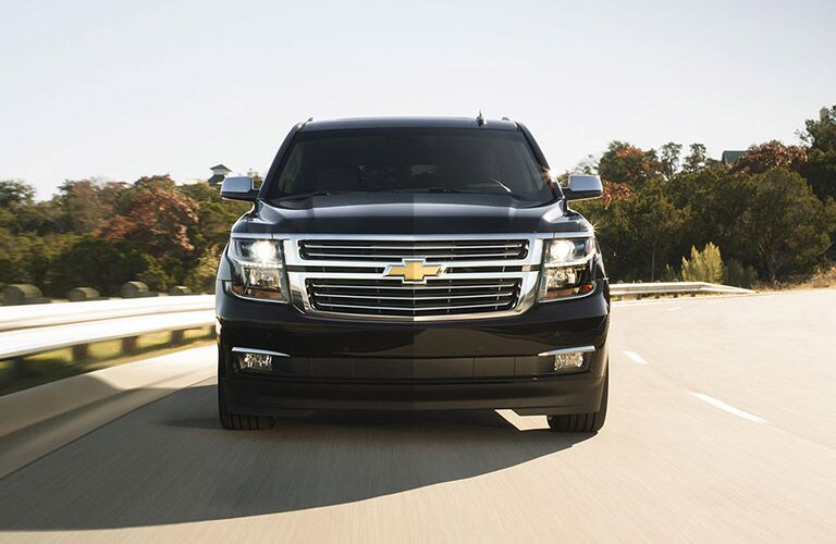 front grille view of a black Chevy Suburban on the road