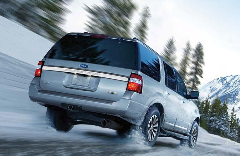 2016 Ford Expedition exterior back fascia and passenger side going fast on snow with blurred pine trees