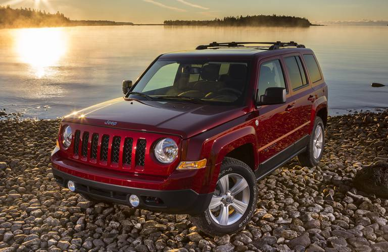 red 2016 Jeep Patriot parked on a rocky beach in front of a lake