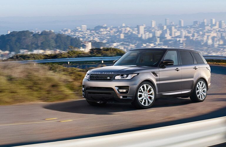 2016 Range Rover Sport exterior front fascia and drivers side driving on road with city in distance