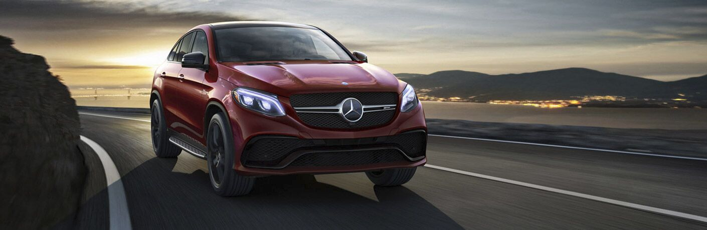 2016 Mercedes-Benz GLE 63 exterior front fascia and passenger side going fast on road with sunset