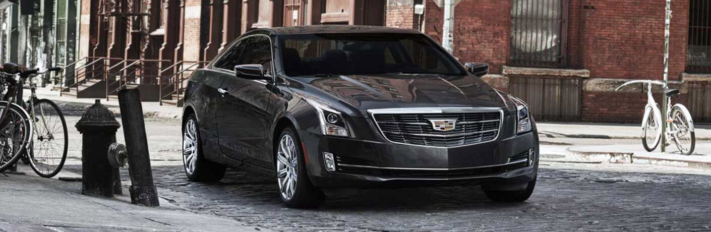 2017 Cadillac ATS sedan exterior front fascia and passenger side parked on road with bike on left