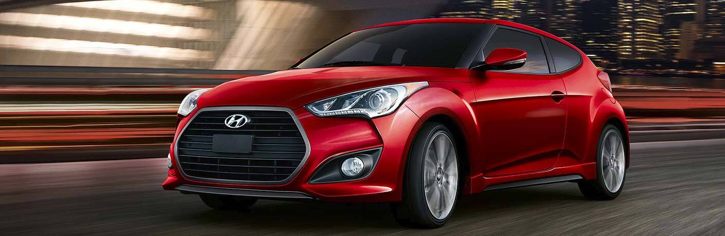 Red 2017 Hyundai Veloster driving down city street at nighttime