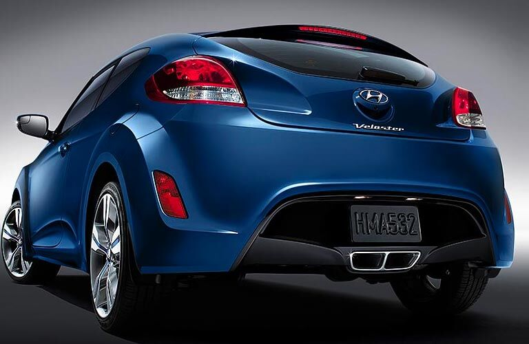 Rear view of blue 2017 Hyundai Veloster on silver background