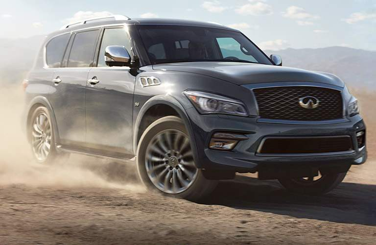 2017 INFINITI QX80 driving through the dust of a desert