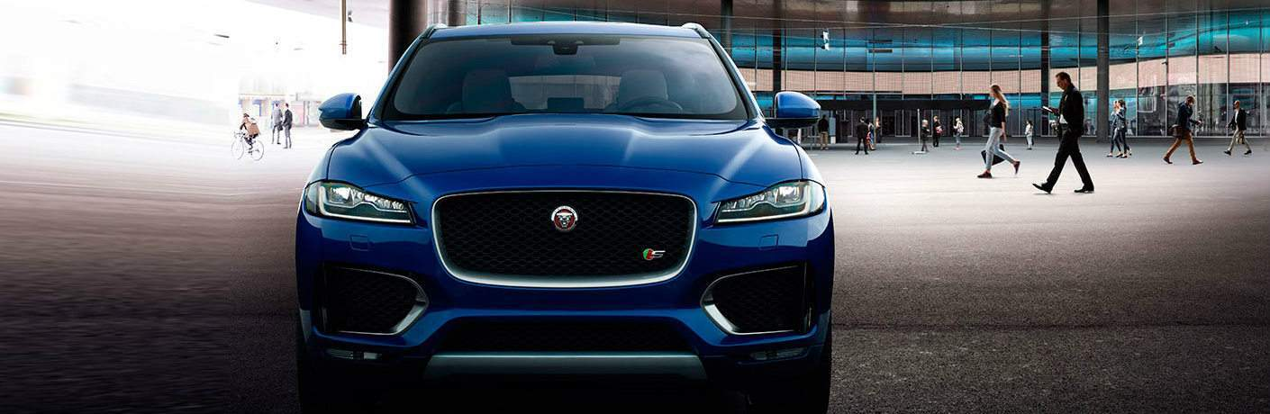 Blue 2017 Jaguar F-PACE Front Grille in Front of Mirrored Building with Pedestrians in the Background