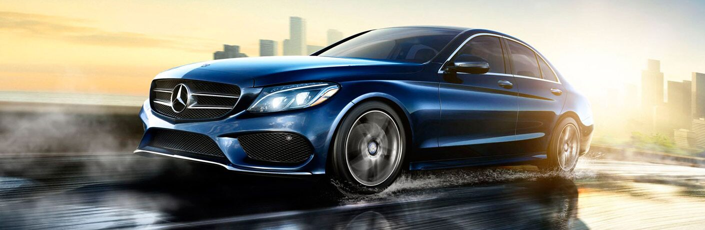 2017 Mercedes-Benz C-Class exterior front fascia and drivers side going fast on city highway after rain