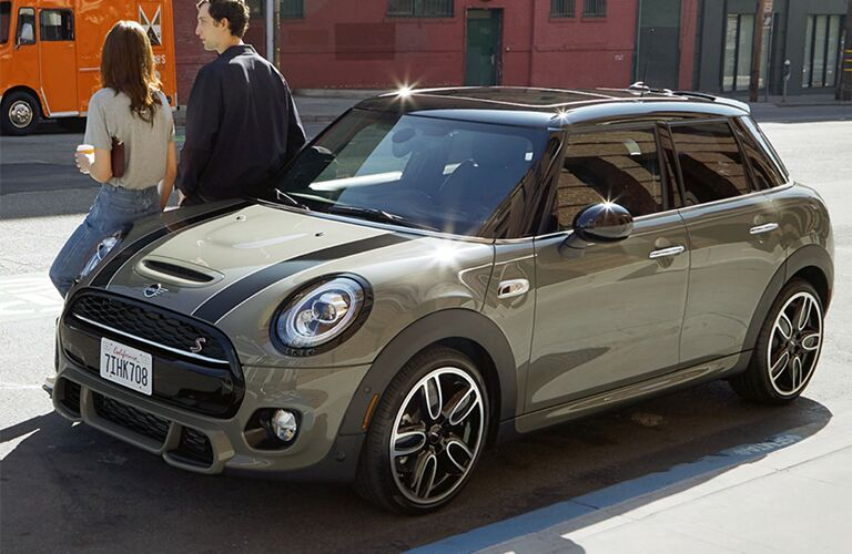 2017 MINI Cooper Hardtop exterior front fascia and drivers side with couple walking next to it