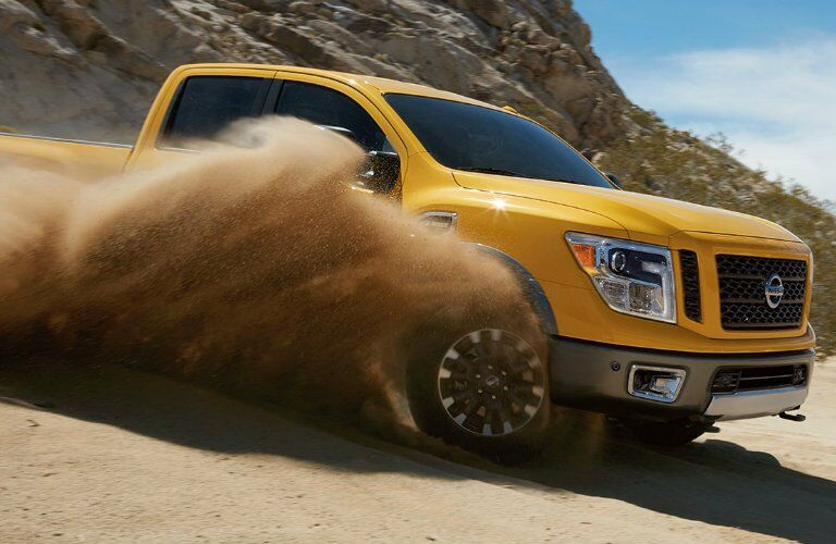 side view of a yellow 2017 Nissan Titan kicking up dirt