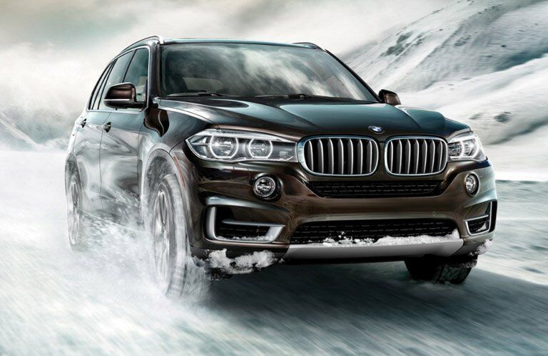 2017 BMW X5 exterior front fascia and passenger side going fast in snow
