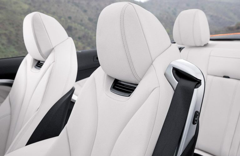 Interior shot of a bmw featuring white seats with the top down