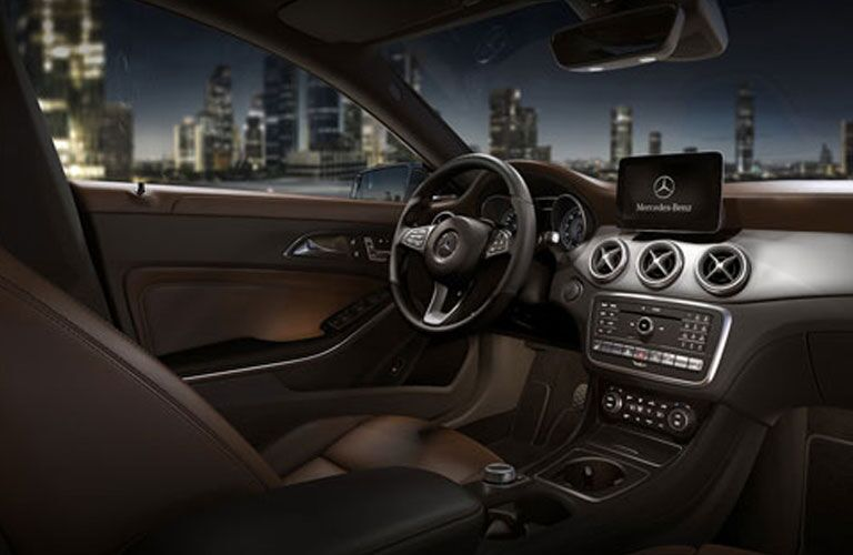 Steering wheel and touchscreen of Mercedes-Benz CLA 250 with city skyline in background