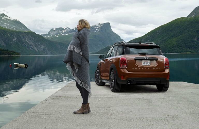 Woman looking at mountainous scenery with MINI Cooper Countryman in view behind her