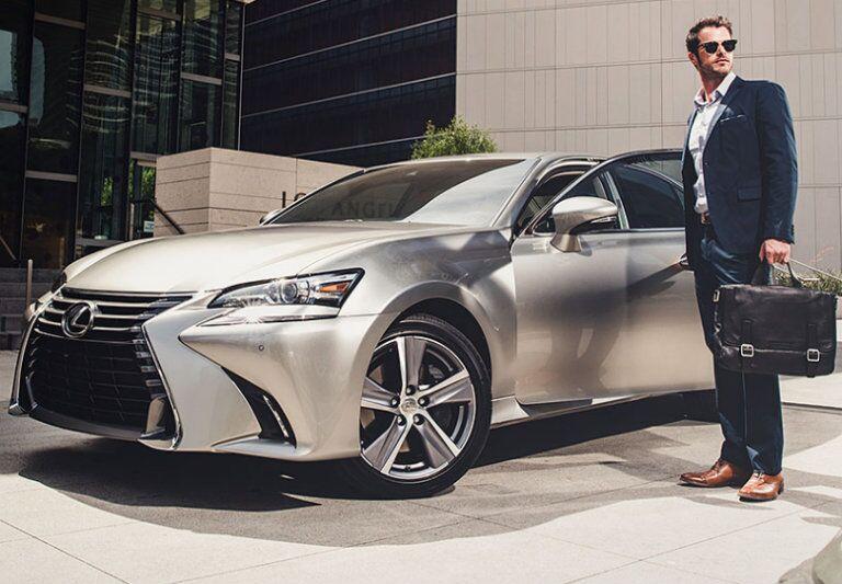 Professionally dressed man standing next to Lexus GS