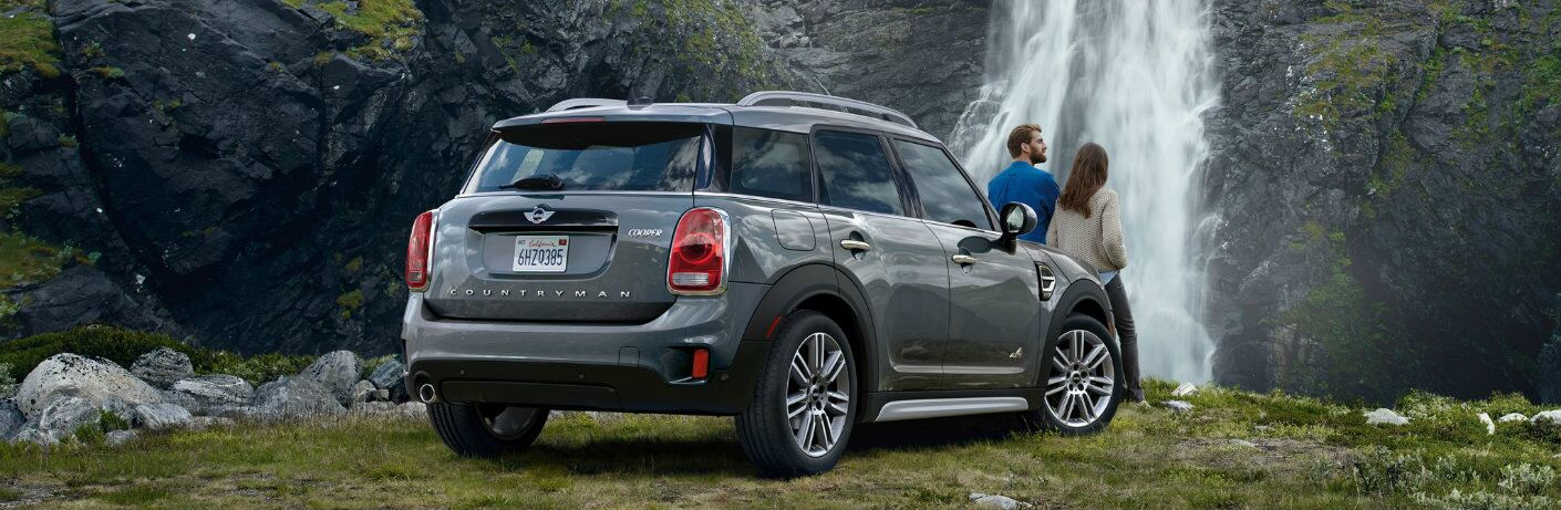 Man and woman leaning against hood of 2018 MINI Cooper Countryman with waterfall in background