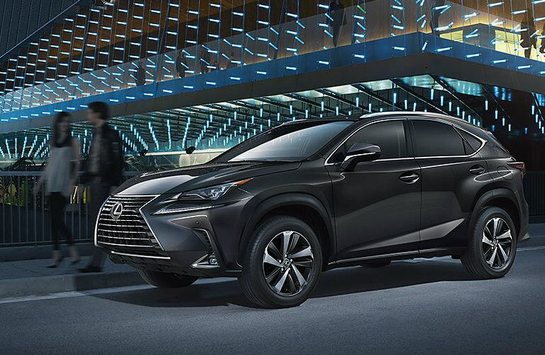 Silver Lexus NX parked in front of modern building at night