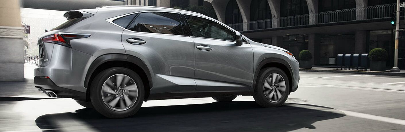 Silver Lexus NX model driving through city intersection in daytime