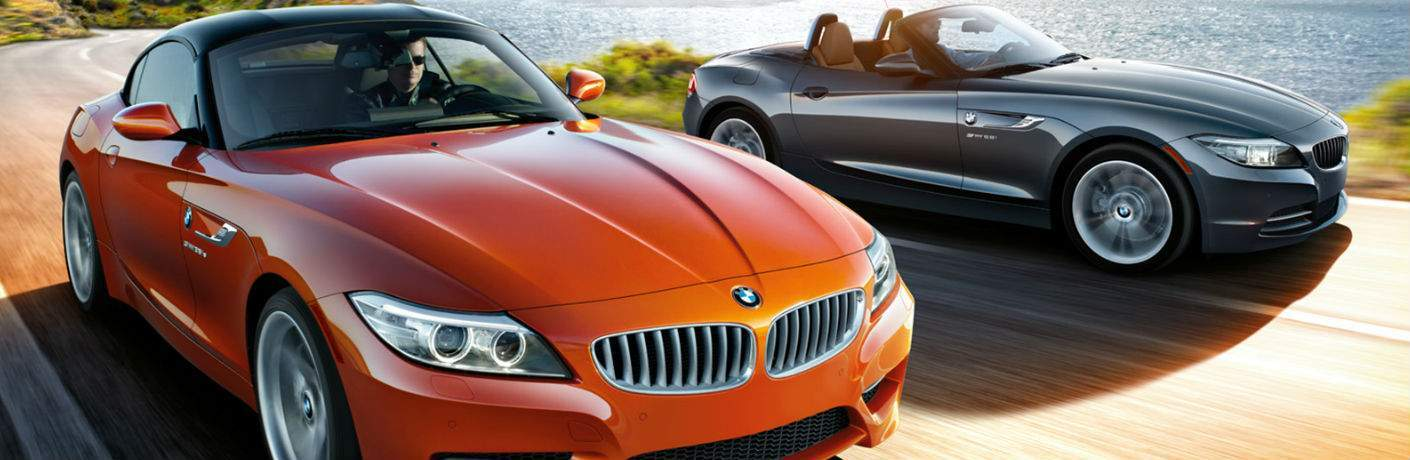 2 2014 BMW Z4 vehicles front fascia and passenger side side by side with man driving the one on the left