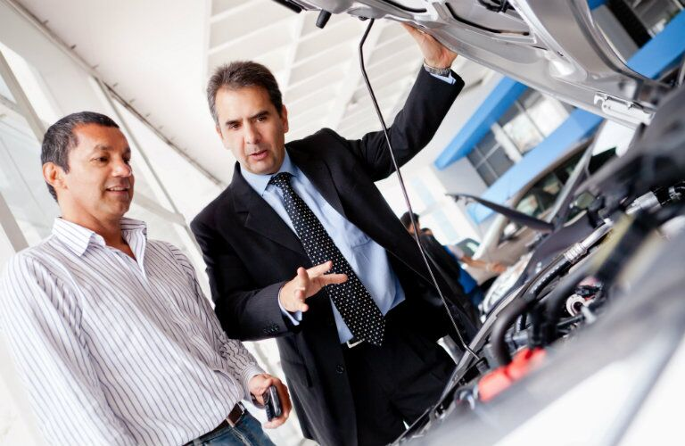 dealership salesman showing a driver a new mazda