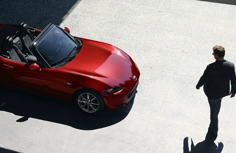 driver walking out to 2016 mazda mx-5 miata in driveway