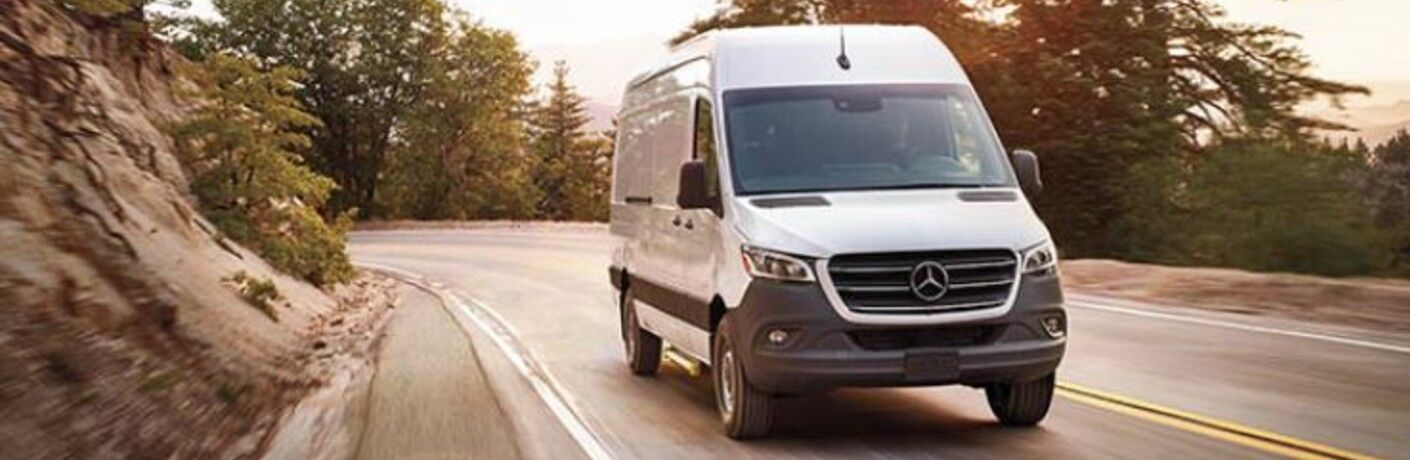 A 2021 Mercedes-Benz Sprinter 1500 Cargo Van driving down a curved road