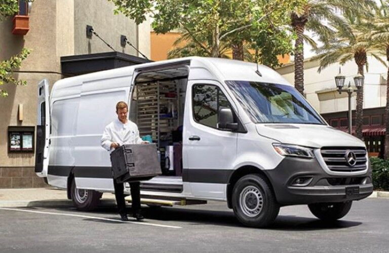 A man unloading materials from the side door of a 2021 Mercedes-Benz Sprinter 1500 Cargo Van