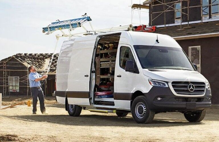 The 2021 Mercedes-Benz Sprinter 1500 Cargo Van at a construction site with a man standing next to it