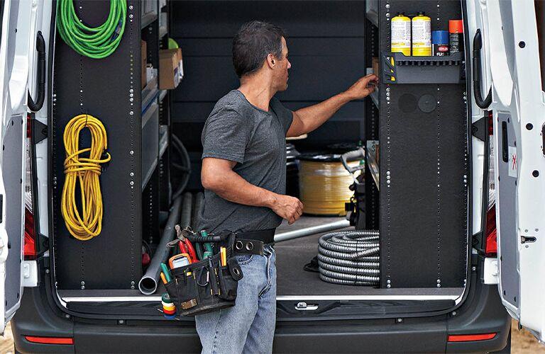 A man unloading the back of a 2021 Mercedes-Benz Sprinter Passenger Van.