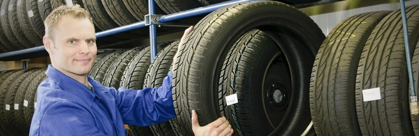 man holding a tire by more tires