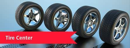"Four tires balance upright on a reflective surface. White text on a red banner reads, ""Tire Center."""